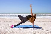 Woman Doing Yoga Exercise On Beach In Vasisthasana Or Side Plank Pose