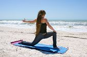 Young Woman Doing Yoga Exercise On Beach Rotated Low Lunge Or Ashwa Sanchalanasana Pose