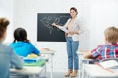 Teacher of geography standing by whiteboard and pointing at outline of piece of land while schoolkid poster