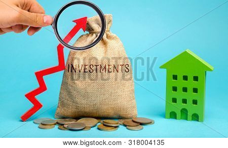 poster of Money Bag With The Word Investments, Up Arrow And Wooden House. The Concept Of Investing In Real Est