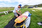 Surfer On Vacation Waxing Surf Board Outdoors On The Beach. Man Is Removing Or Applying Wax To Surfb poster