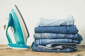 Stack Of Clothes And Electric Iron On Table Indoor. Household Concept. Fresh Folded Cotton Jeans Clo poster