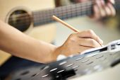 Close-up Shot Of Hand Of A Guitarist Taking Notes While Composing Music poster