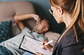 Photo of unshaven caucasian man lying on sofa and having conversation with psychologist on therapy s poster