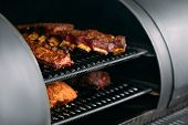 Professional Kitchen Appliance. Poultry, Beef And Pork Meat, Ribs Cooked In Bbq Smoker. poster