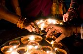 Macro Shots Of Diyas Being Lit By Hand Or Candle For The Hindu Religious Festival Of Diwali. poster
