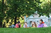 Children And Education, Group Of Schoolchildren Doing Homework On The Lawn. poster
