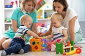 Group Of Babies Play Together With Mothers In The Classroom In Nursery Or Preschool poster