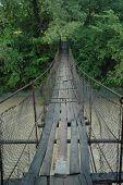 stock photo of shaky  - Shaky wire bridge over a mountain stream - JPG