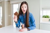 Beautiful Asian woman drinking chocolate milkshake and holding chocolate bar scared in shock with a  poster