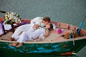 image of wedding couple  - young couple in wedding dress kissing in the boat - JPG