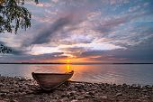 Picturesque Seascape With A Boat On The Shore On The Background Of An Idyllic Sunset. poster