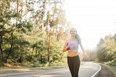 Beautiful Caucasian Young Girl Athlete Runs Sunny Summer Day On Asphalt Road In The Pine Forest. Wom poster