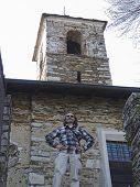 stock photo of salvatore  - smiling man under the San Salvatore tower in Massino Visconti Italy - JPG