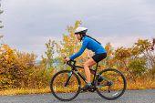 Biking woman doing gravel road bike  in autumn. Active sport girl doing fitness exercise in fall sea poster