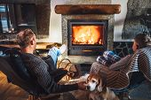 Father With Son Sitting In Comfortable Armchairs In Their Cozy Country House Near Fireplace And Enjo poster