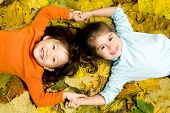 stock photo of young girls  - Two young girls playing in the Autumn Leaves - JPG