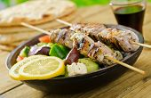 stock photo of souvlaki  - A delicious grilled pork souvlaki served with greek salad - JPG