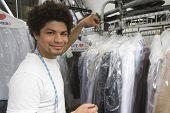 Portrait of a young mixed race man working in dry cleaning store