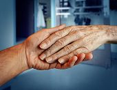 pic of retirement age  - Elderly care and senior health services with the hand of a young person holding and helping an old and aging retired patient needing in home medical help due to aging and memory loss in a hospital background - JPG