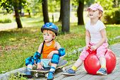 Little boy in protective equipment sits on skateboard and little girl sits on red ball for jumping o