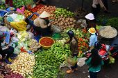People buy and sell vegetables  at open air market
