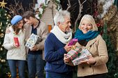 Portrait of happy senior couple holding Christmas presents with children standing in background at s