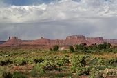 picture of windswept  - Red sandstone peaks and plateaus of La Sal Mountains with foreground of wild desert. Copy space in blue sky with windswept white clouds.