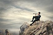 rich businessman sitting on a chair in the mountain looking the landscape with spyglass