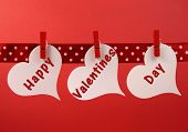 Happy Valentines Day Message Greeting Written Across White Heart Tags Hanging From Red Pegs On A Lin