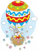 stock photo of cony  - Little rabbit flies in an air balloon colored like an Easter egg and scatters flowers around - JPG