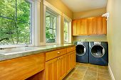 image of laundry  - Narrow laundry room with wooden cabinets washer and dryer - JPG