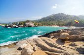 picture of tropical rainforest  - Tropical beach in Tayrona National Park in Colombia with a Colombian flag visible - JPG