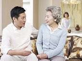 pic of mother law  - asian mother and adult son chatting on couch - JPG