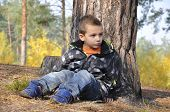 Forest Little Boy Sits Near A Pine.