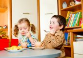 stock photo of tea party  - Boy and girl sitting at the table and having tea with cookies - JPG
