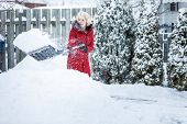 foto of shovel  - Woman Shoveling her Parking Lot after a Snowstorm - JPG