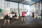 picture of jerks  - Crossfit instructors assisting athletes in lifting barbells in fitness box - JPG