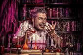 stock photo of scientist  - Crazy old man medieval scientist working in his laboratory - JPG