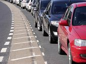 stock photo of bend  - A row of parked cars curving around bend in road - JPG