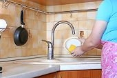 stock photo of pinafore  - Woman housewife washing plate in the kitchen - JPG