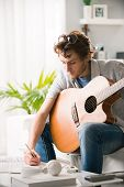 image of compose  - Young man playing guitar and composing a song sitting on sofa - JPG