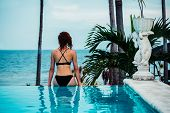 image of infinity pool  - A young woman is sitting by the edge of an infinity pool by the ocean - JPG