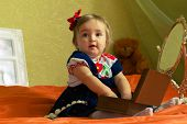 picture of casket  - dressed small girl plays with casket and looks at camera - JPG