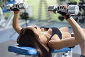 picture of dumbbell  - Young woman training in a gym with dumbbells - JPG