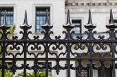 picture of spike  - Old ornamental wrought iron fence with spiked tops in front of stone building - JPG