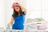 stock photo of laundry  - Young woman ironing on ironing board in front of her is full laundry basket with an expression of dissatisfaction with one hand holding her head - JPG
