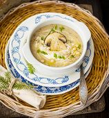 stock photo of spores  - porcini soup puree with pine nuts in a white plate on a wicker tray on a wooden background with herbs - JPG