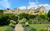 stock photo of slating  - An English manor built out of Cotswold stone with stone tiles on the roof called slates with a garden full of flowers and a grass lawn in Chipping Campden the Cotswolds England UK - JPG