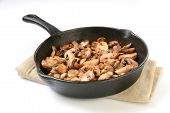 picture of sauteed  - Sauteed mushrooms in a cast iron skillet on a white background - JPG
